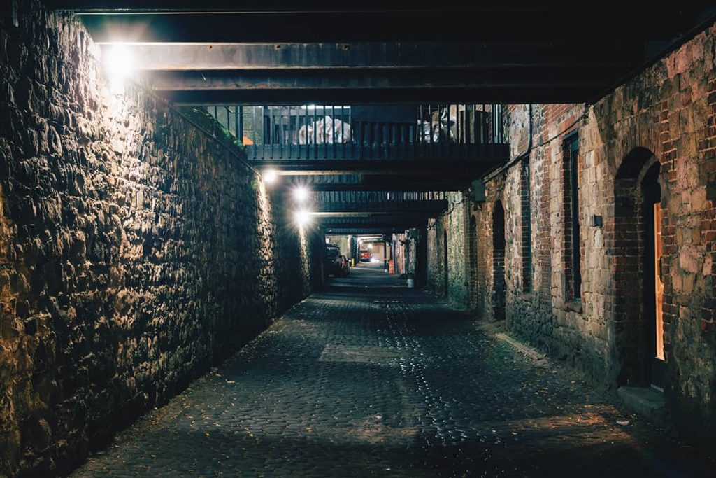 Dark and eerie lower-level alley at night surrounded by brick walls on two sides and old iron crosswalks above