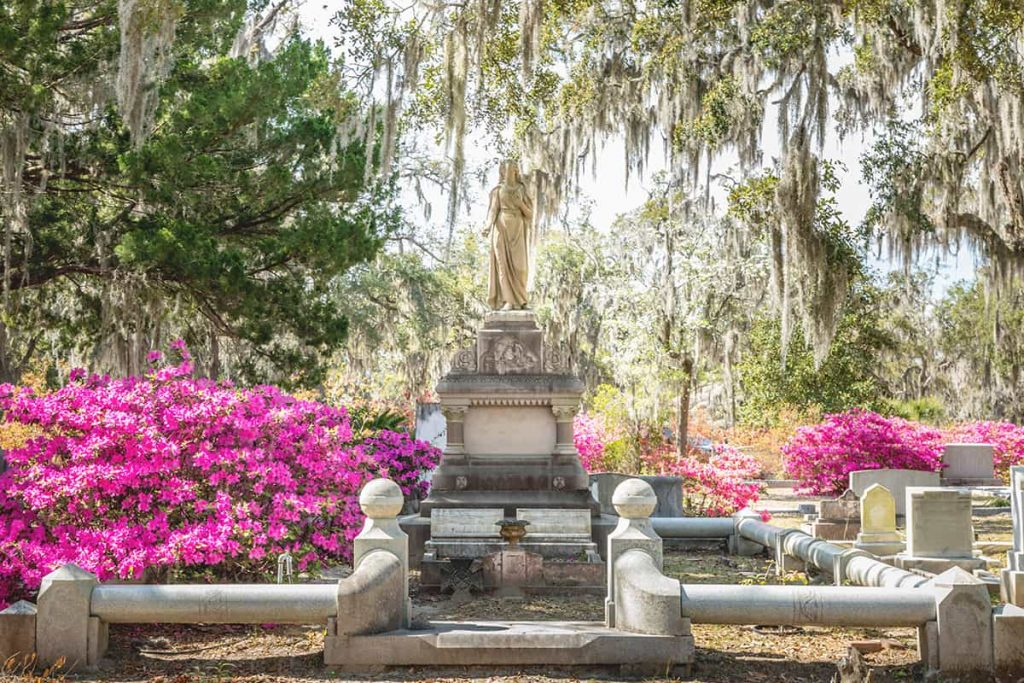 Elaborate statue grave marker surrounded by bright pink azaleas and oak trees draped with Spanish moss
