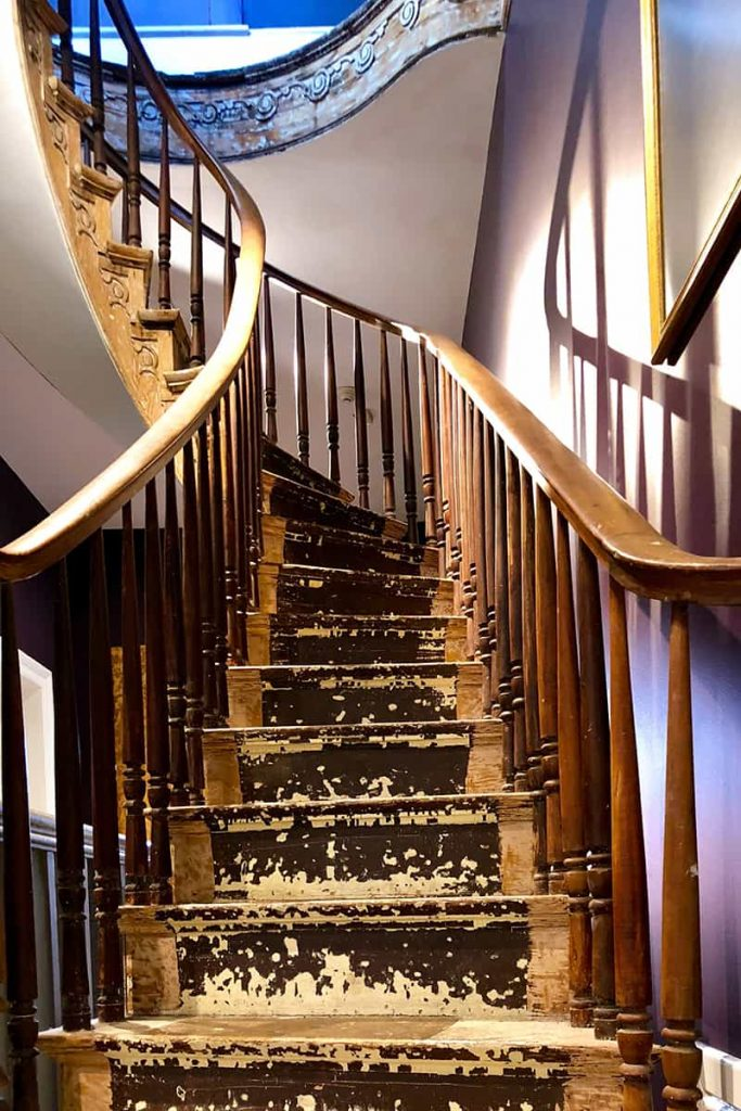 An old wooden spiral staircase with paint and stain chipping off the treads