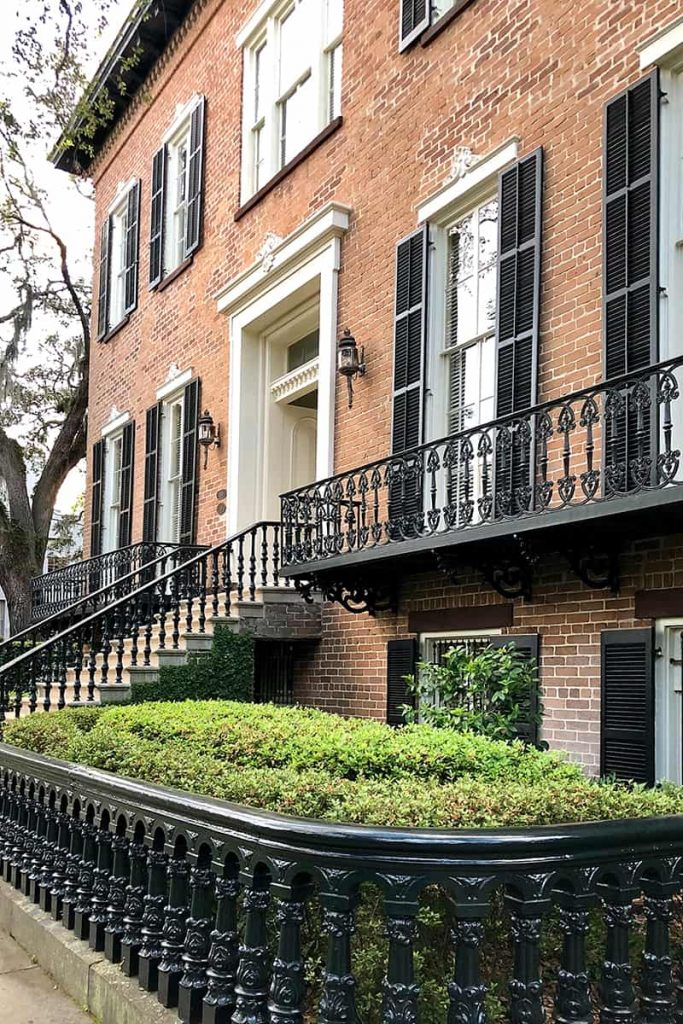 Side view of a multi-story classic brick home with cast iron railings and an imposing entry