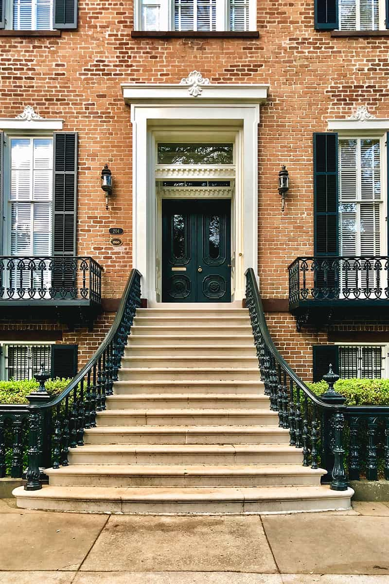 Grand staircase with at least 12 stairs and a cast iron railing leading up to an imposing set of double doors inset into a stately brick house