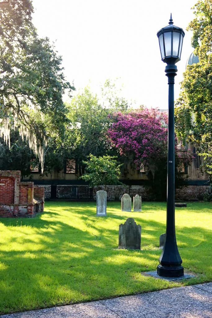 Cemetery scene with old headstones, a lamppost, and Spanish moss dangling from the trees.