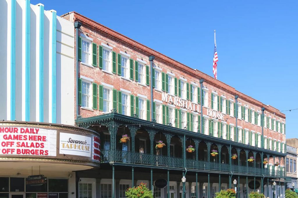 Four story hotel with a cheery red brick exterior, green shutters and a long front porch