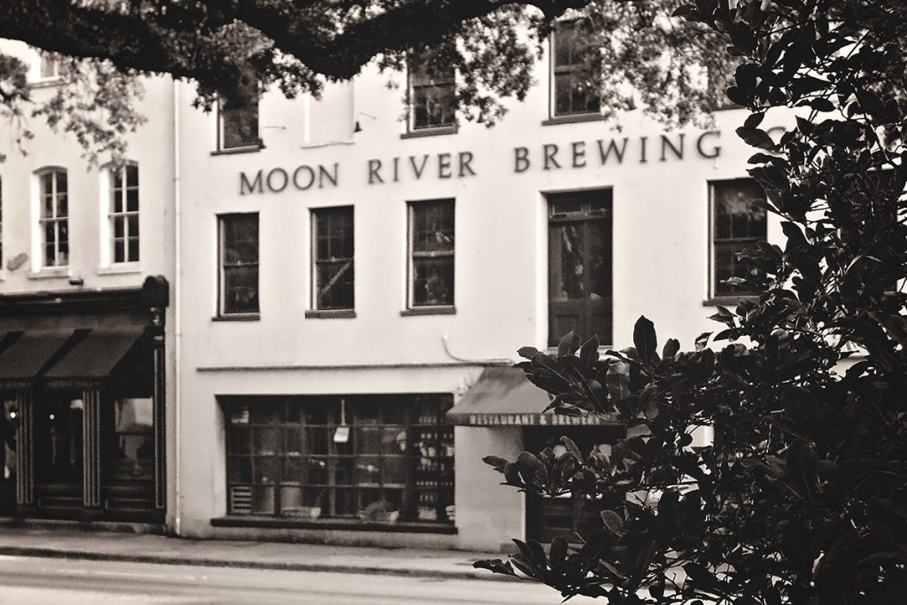 Peeking through the trees at a four-story building labeled Moon River Brewing