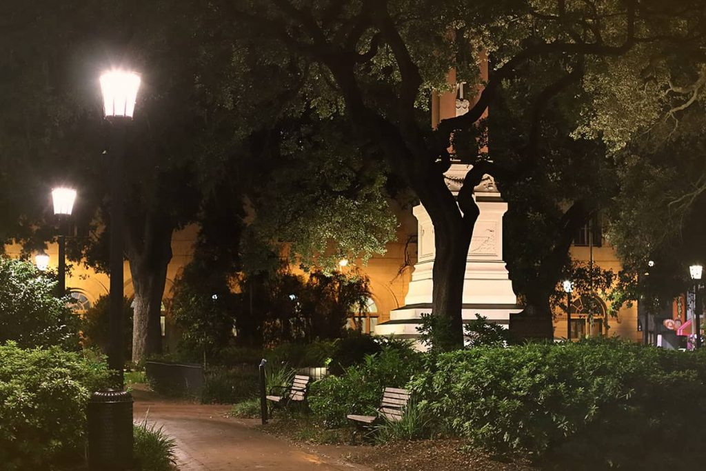 Haunted Wright Square at night with gas lanterns illuminating red brick sidewalks