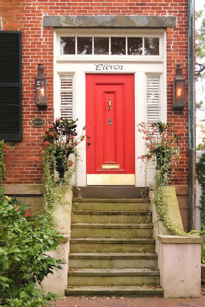 Moss-covered stone steps leading up to a cheery bright red door with the word Eleven written in script above it