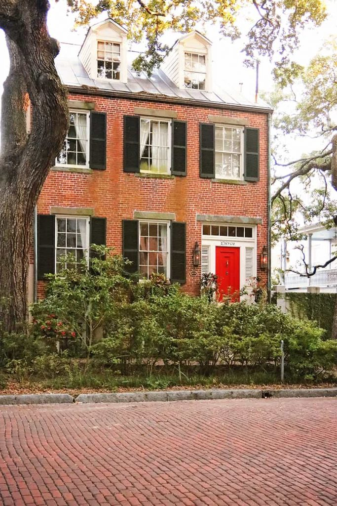 Three-story brick home with a bright red door and black shutters
