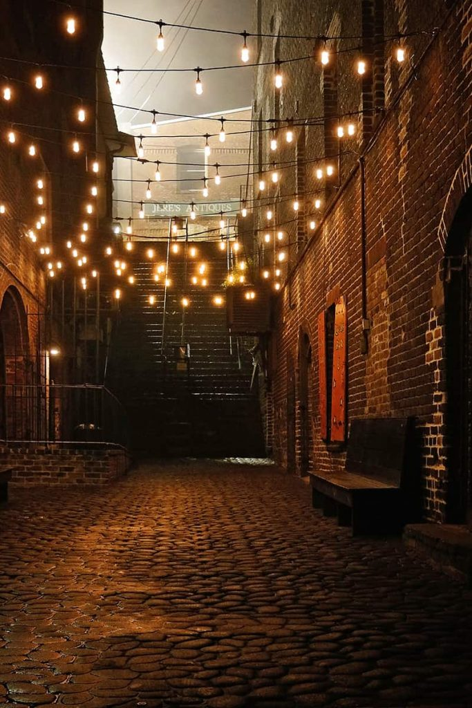 Dimly lit alley at night with stairs leading to mist in the background