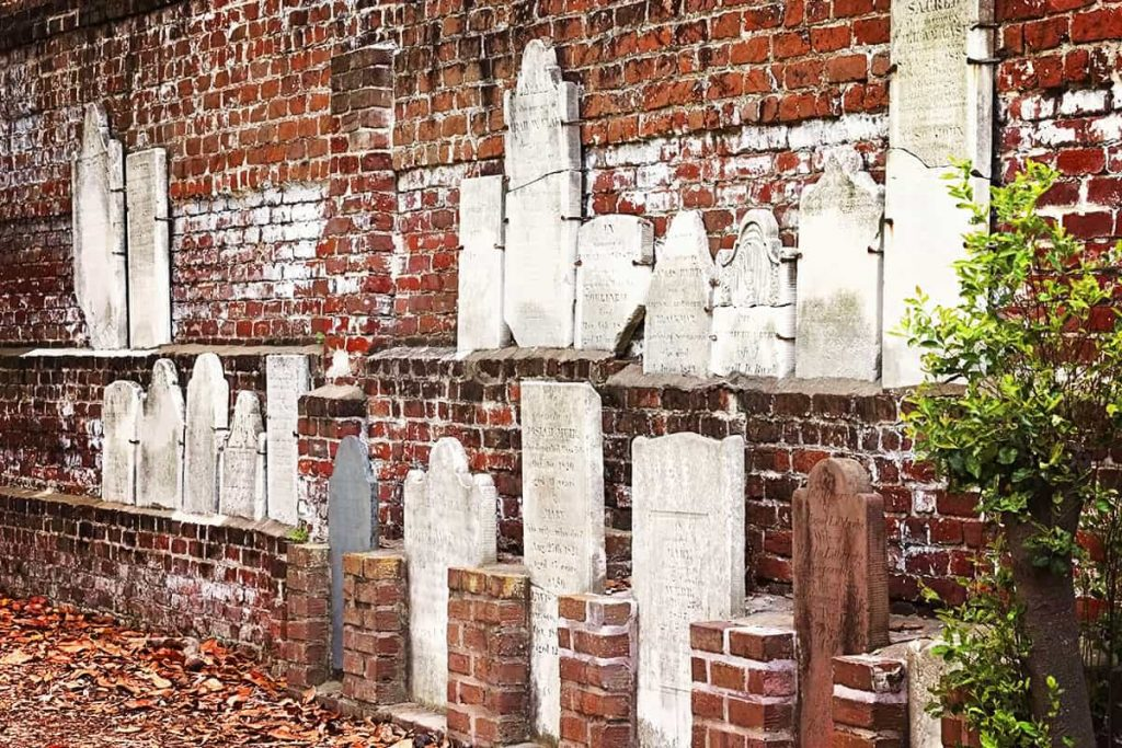 Red brick wall with numerous old white headstones propped against it
