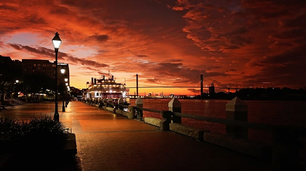 River Street Savannah GA with a fiery red and orange stormy sky in the background