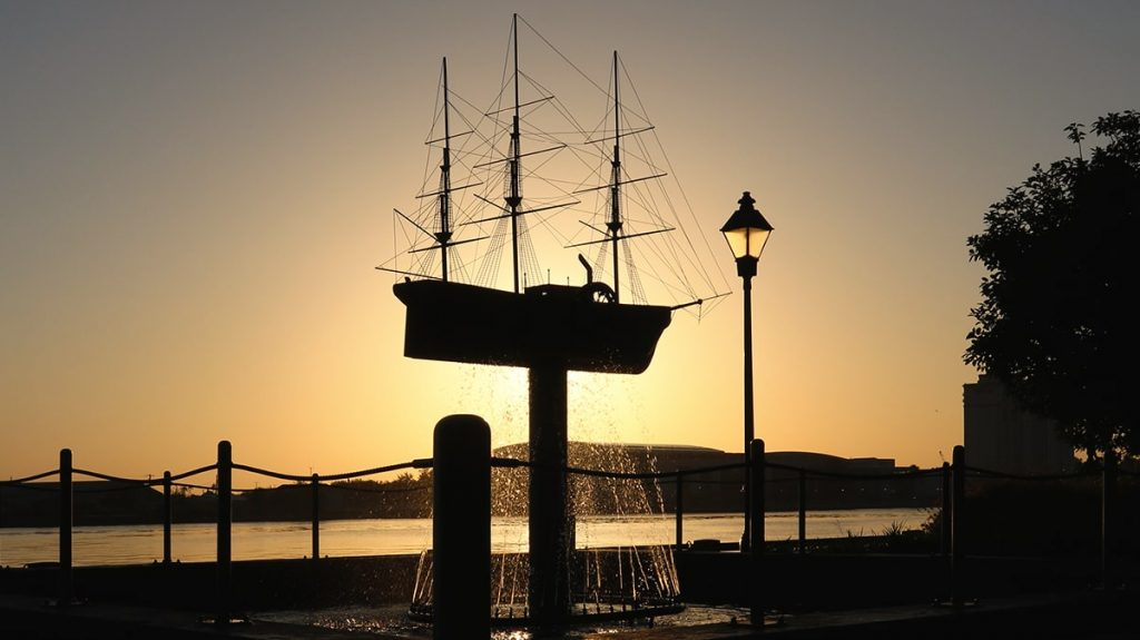 Ship fountain sillhouetted against a golden sunrise on River Street Savannah GA