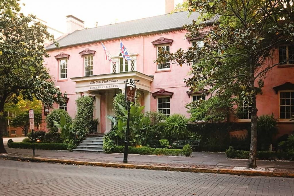 Stately two-story pink stucco home with flags displayed over the front portico