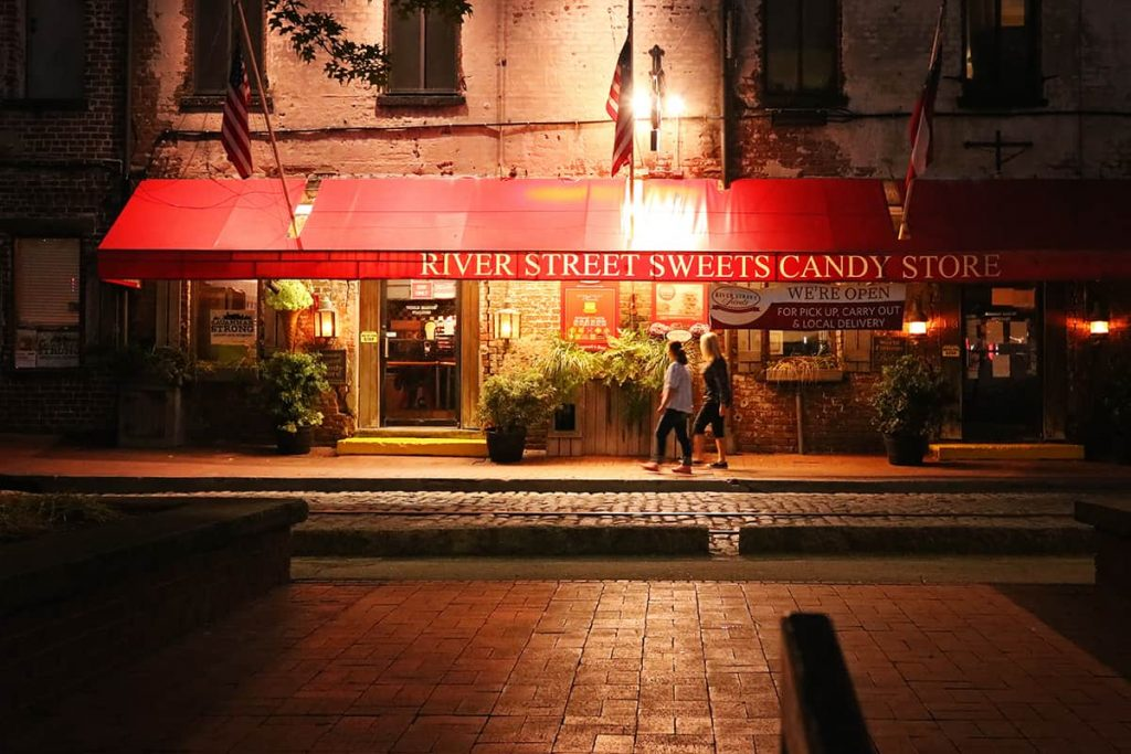 Candy shop with a red awning dimly lit at night with two women passing by