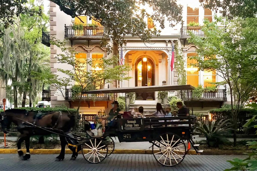 The Hamilton-Turner Inn surrounded by trees with a horse and carriage passing by the front steps