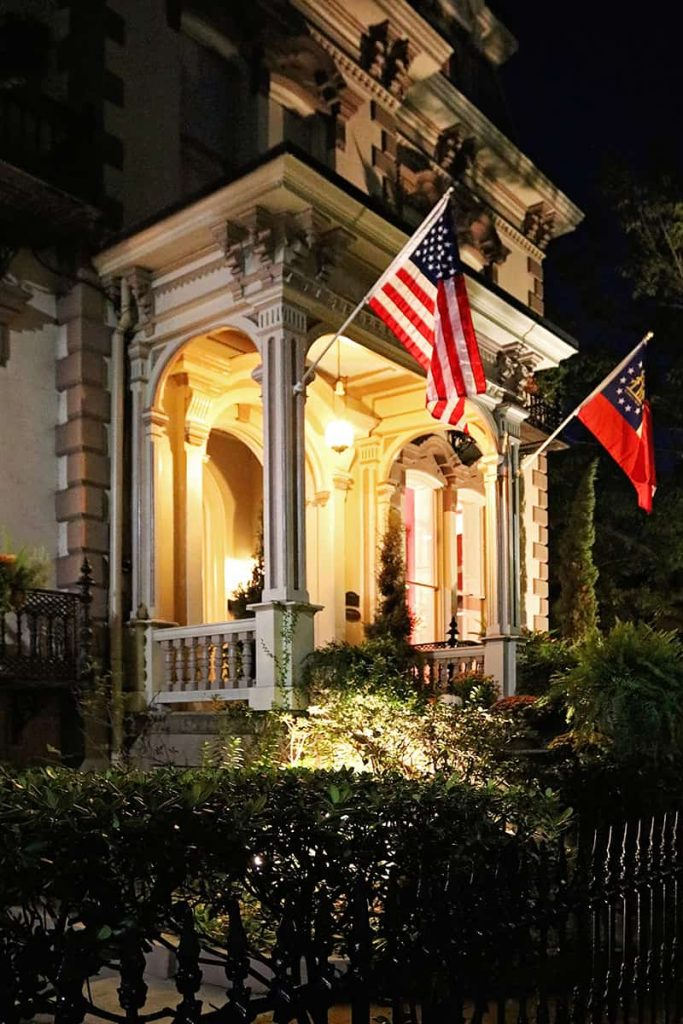 Front entrance to the Hamilton-Turner Inn lit up at night with two flags on display over the porch