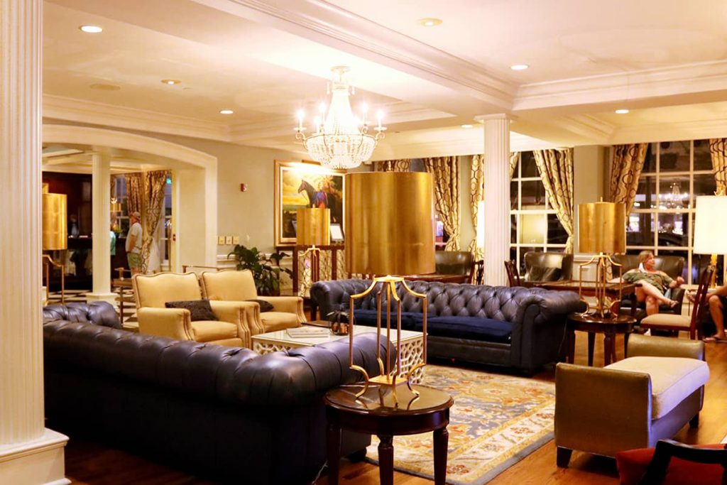 The warmly lit lobby of The Marshall House in Savannah with two navy blue leather couches, gold upholstered chairs, a beautiful chandelier, and nice artwork on the walls