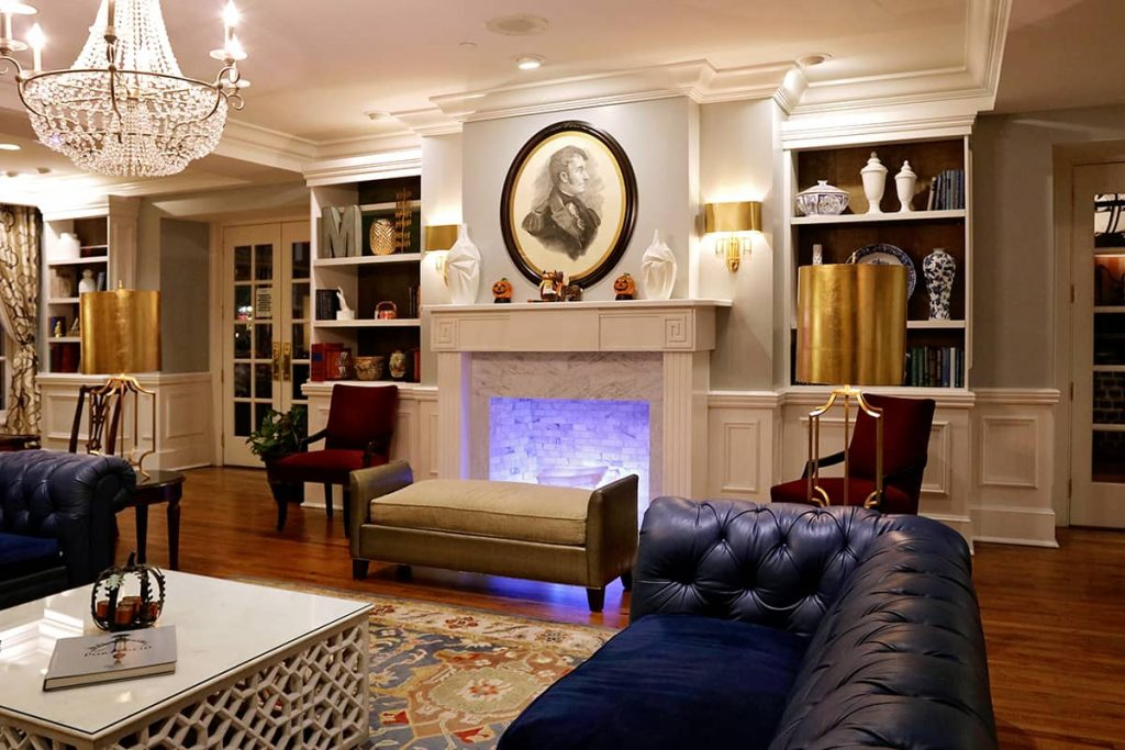 Warm and welcoming lobby of The Marshall House in Savannah GA with a fireplace surrounded by bookshelves and two blue leather couches nearby