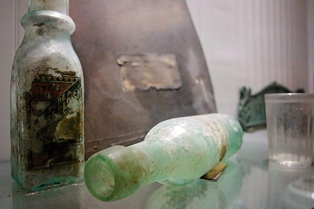 Old green glass bottles and an old leather bound journal on display next to a bottle with the label partially destroyed