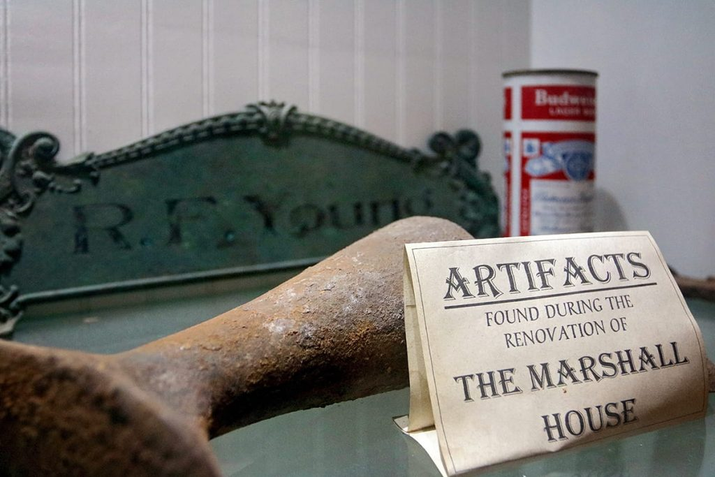 Sign denoting artifacts found during the renovation of The Marshall House coupled with an old sign, a rusted tool, and an antique Budweiser can