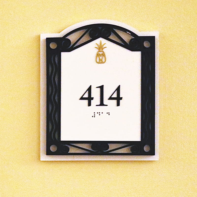 White sign with black frame and a gold pineapple above the room number 414