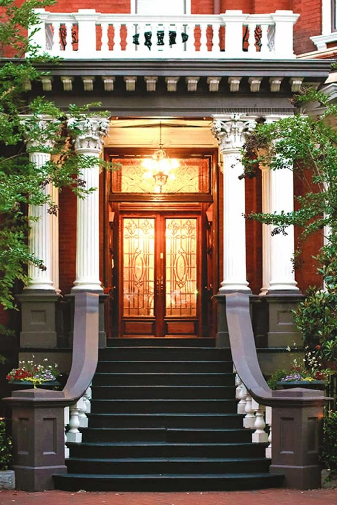 Grand front entrance to The Kehoe House with elaborate white columns supporting a porch over the stairs