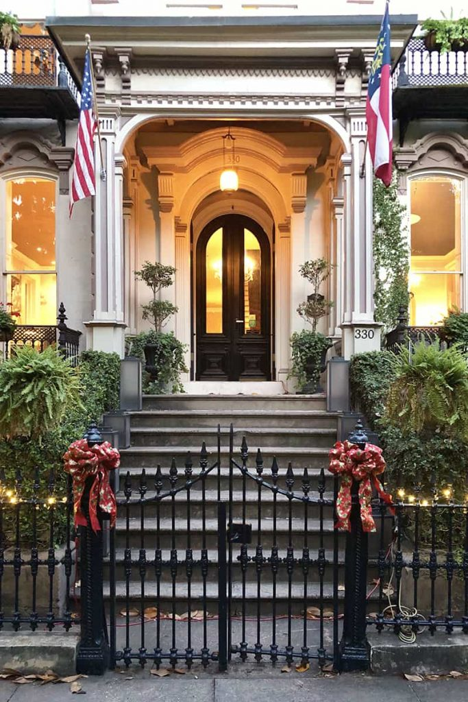 The Hamilton-Turner Inn front entrance with flags flying on each side of the portico and beautiful red bows tied on each side of the gate