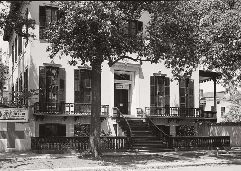 Historic photo of the Abram Minis House in the 1930s with Red Cross signage hanging out front