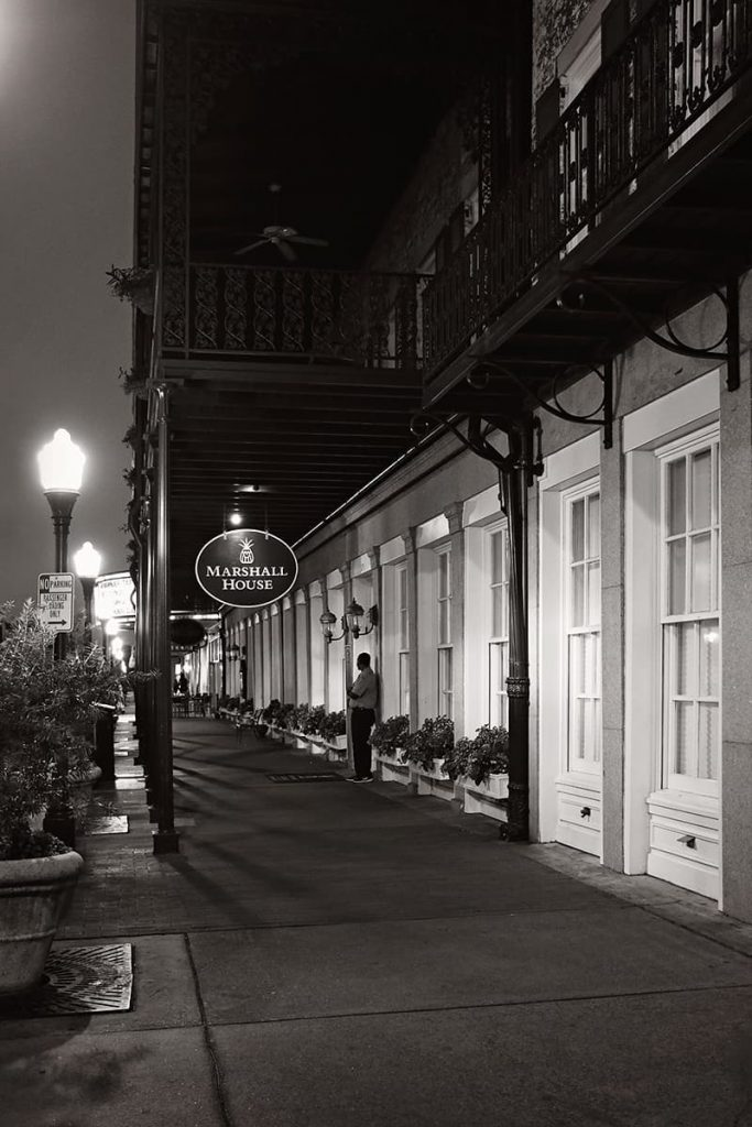 Nighttime view of the front facade of The Marshall House Savannah with an empty streetlit sidewalk and one lone bellhop by the door