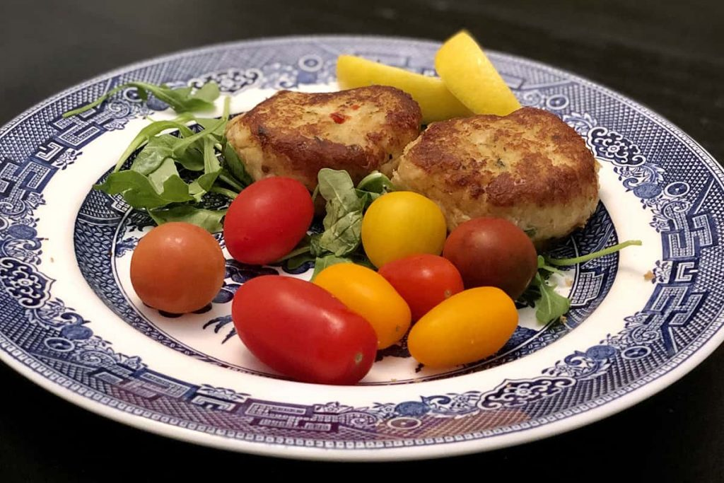 Blue and white china with two crabcakes and colorful red yellow and orange tomatoes