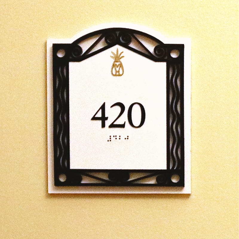 White sign with gold pineapple and black frame with the number 420