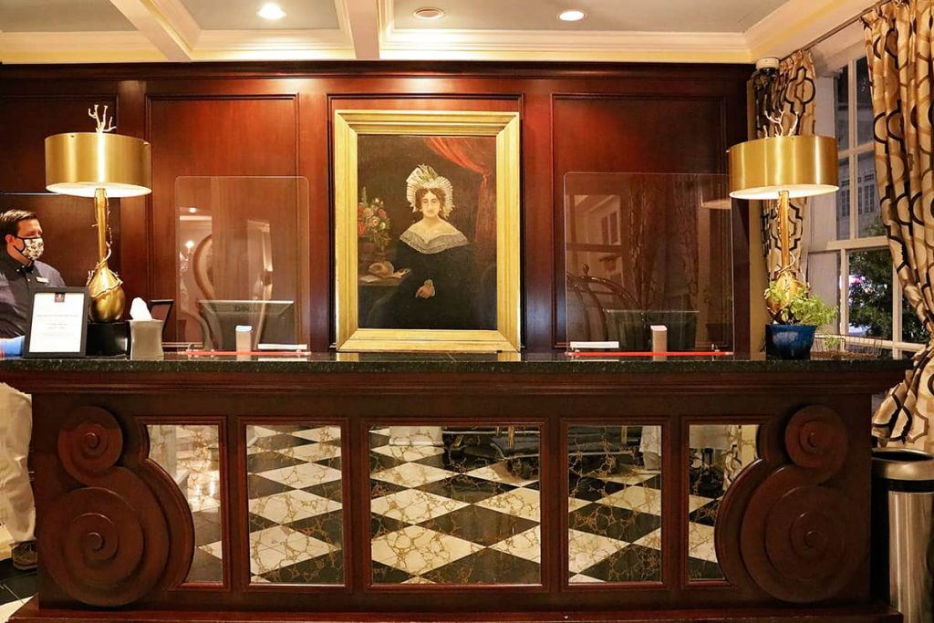 Mahogany check-in desk at The Marshall House with a painted portrait of Mary Marshall in a gold frame above the desk