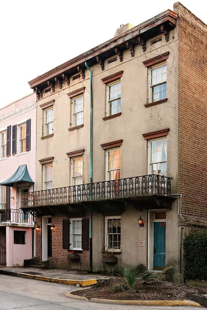 Three-story brown stucco and brick home with a blue door and an iron balcony on the second floor