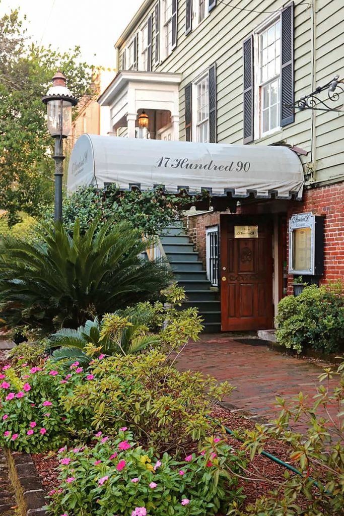 Front entry with flowers and a wooden door with a gray awning with signage that reads 17Hundred90