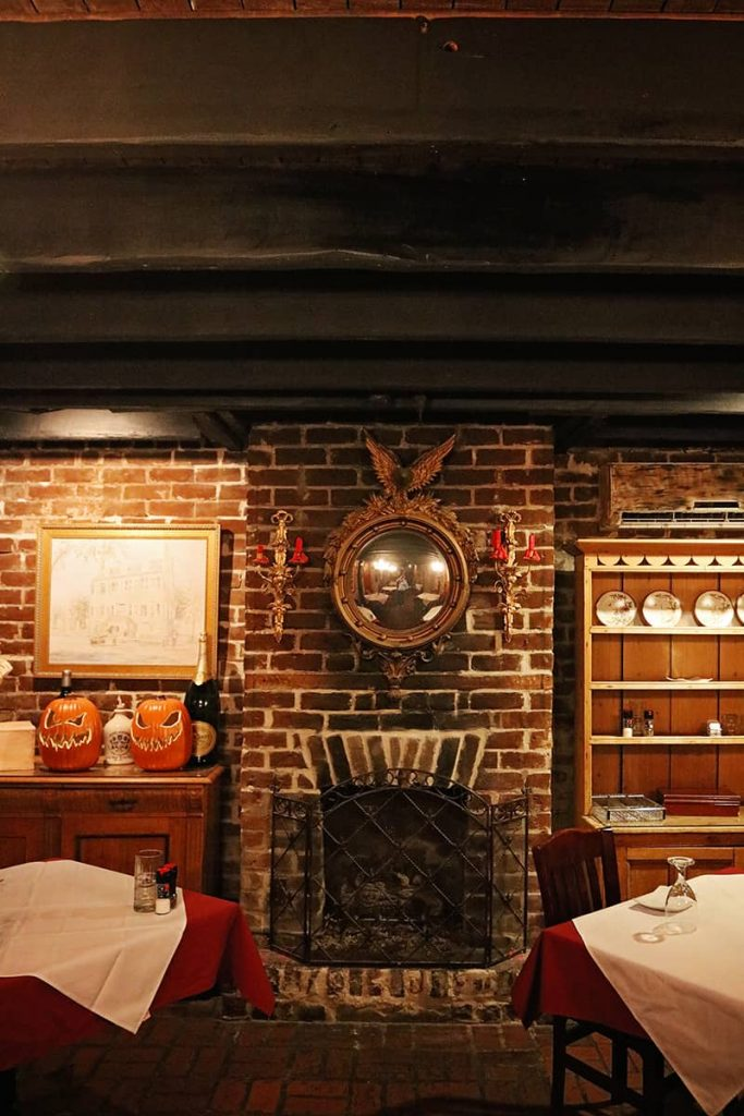 Low wood-beam ceilings above a fireplace with gold-framed mirror at the haunted 17Hundred90 Inn and Restaurant.