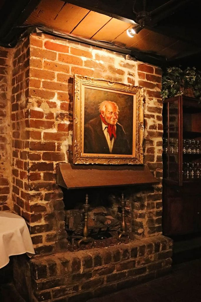 Old fireplace with an oil painting of an old, balding man wearing a red kerchief tied around his neck