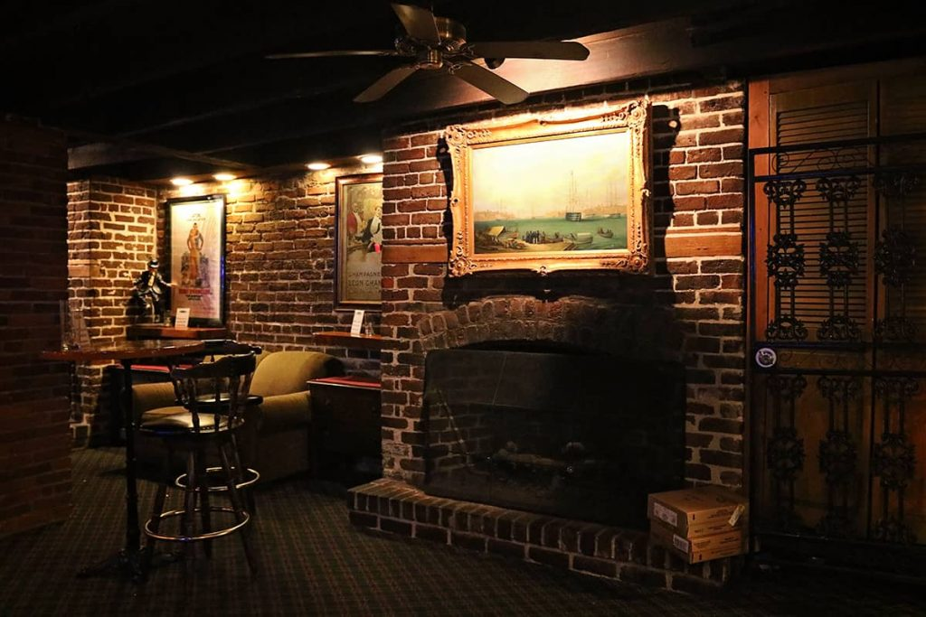 Cozy seating area in a bar with brick fireplace, oil paintings of old ships, and dim lighting