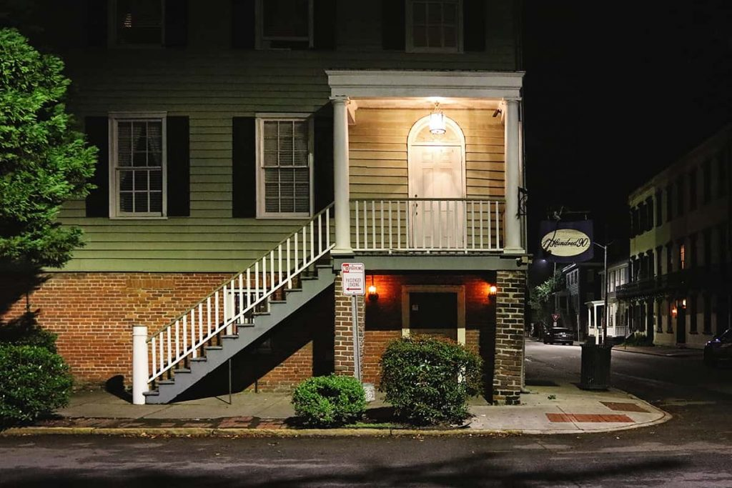 Entrance to the 17Hundred90 Inn with a brown brick first floor and green wooden upper floors with black shutters
