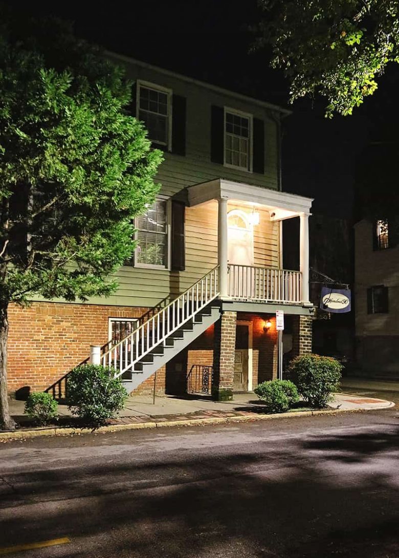 Three-story inn lit up at night with spooky lighting