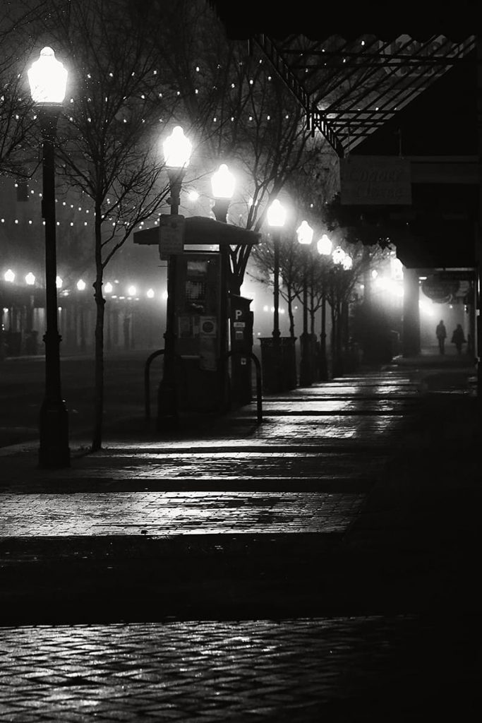 Nighttime scene along Broughton Street with street lamps glowing in the mist and a silhouette of two people in the distance