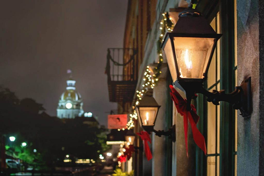 A Christmas in Savannah scene with flickering lanterns on the side of River Street Inn adorned in red ribbons and greenery