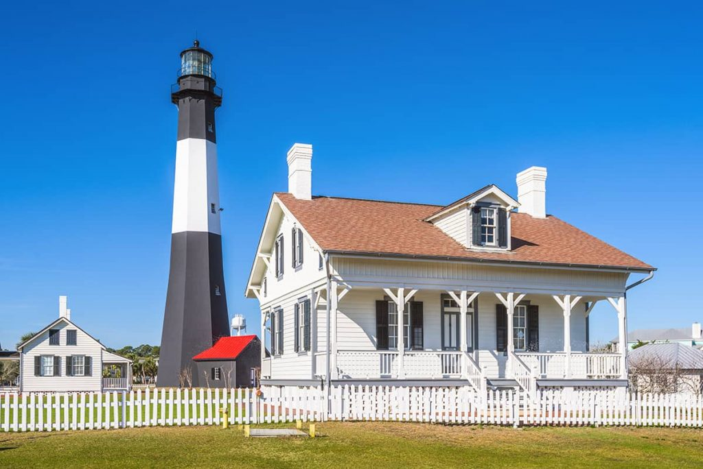 White cottage with a black and white lighthouse behind it and deep blue skies in the background