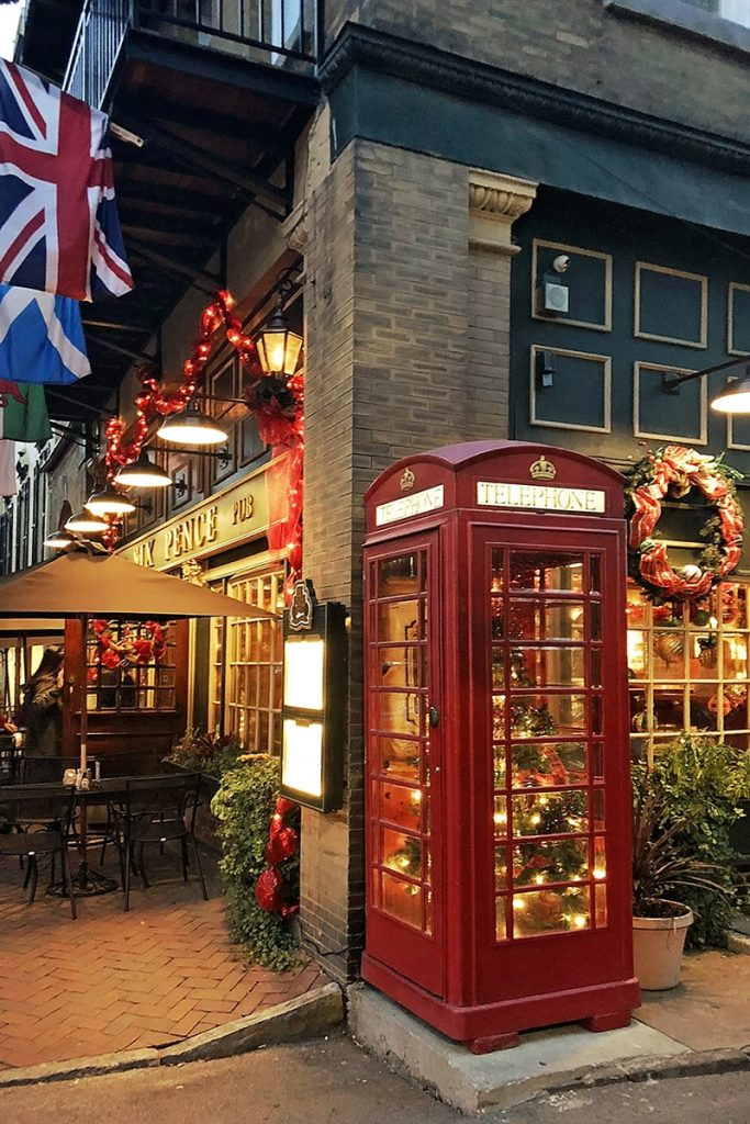 Six Pence Pub with a lit Christmas tree inside a red telephone booth, a wreath over a window, and red ribbons and colorful flags hanging over the front entrance