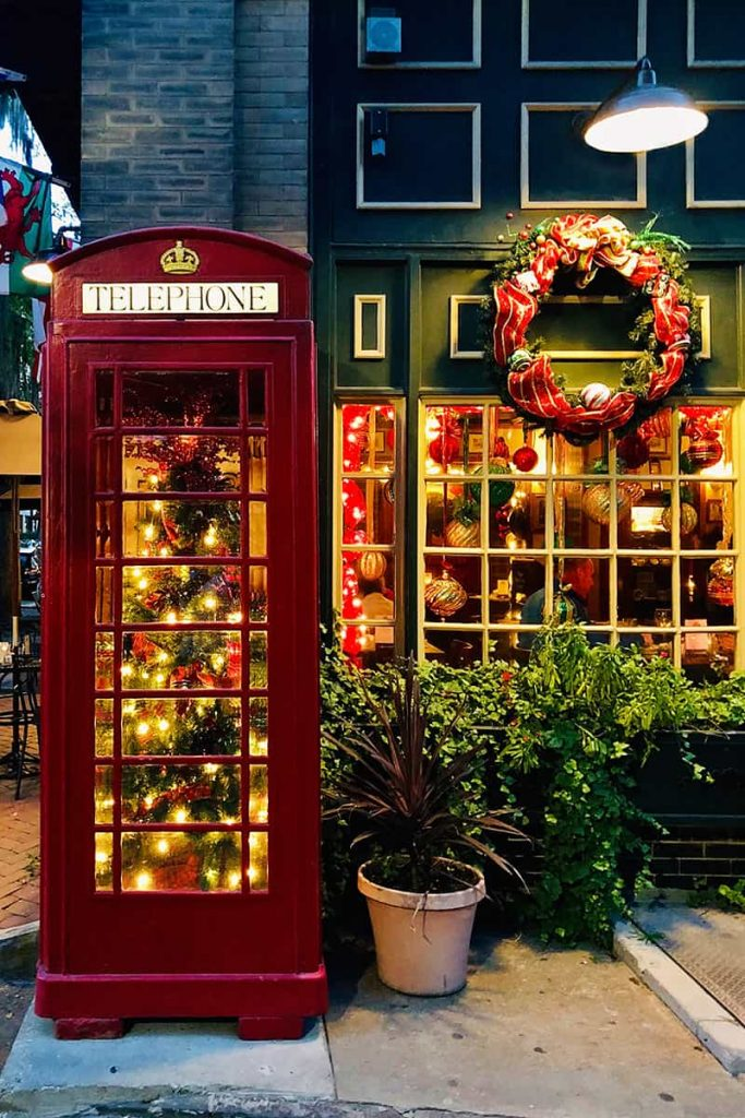 Six Pence Pub with a lit Christmas tree inside a read telephone booth, a wreath hung over a window, and ornaments hanging fro, the interior of the windows