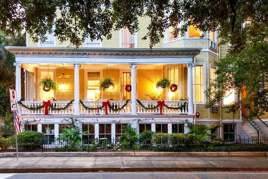 Christmas in Savannah at The Forsyth Inn, a cheery yellow B&B with a white porch decorated with red ribbons and greenery