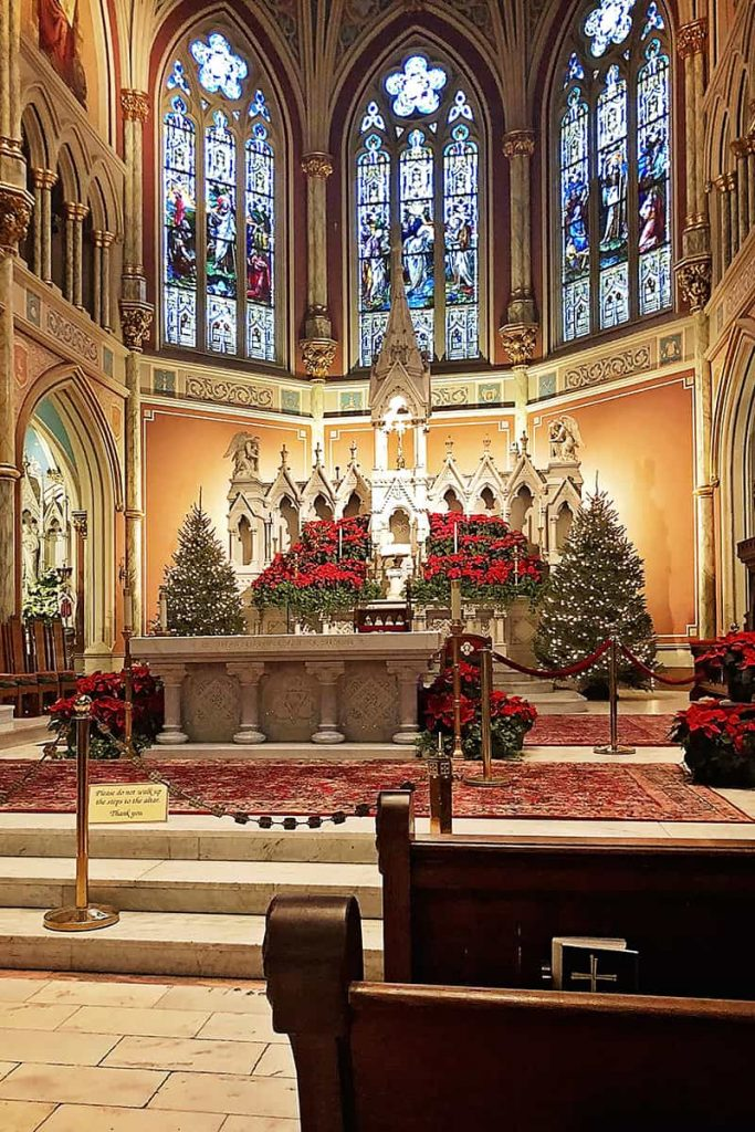 Interior of the Cathedral Basilica of St. John the Baptist with large stained glass windows, Christmas trees, and poinsettias