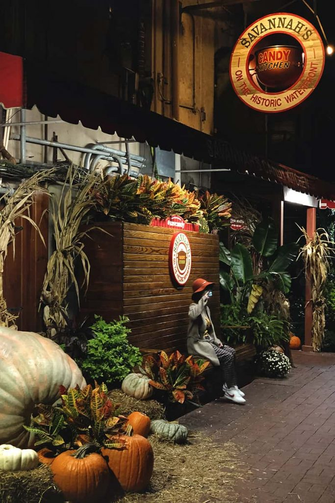 Savannah Candy Kitchen exterior decorated with oversized pumpkins, bales of hay, and fall decor