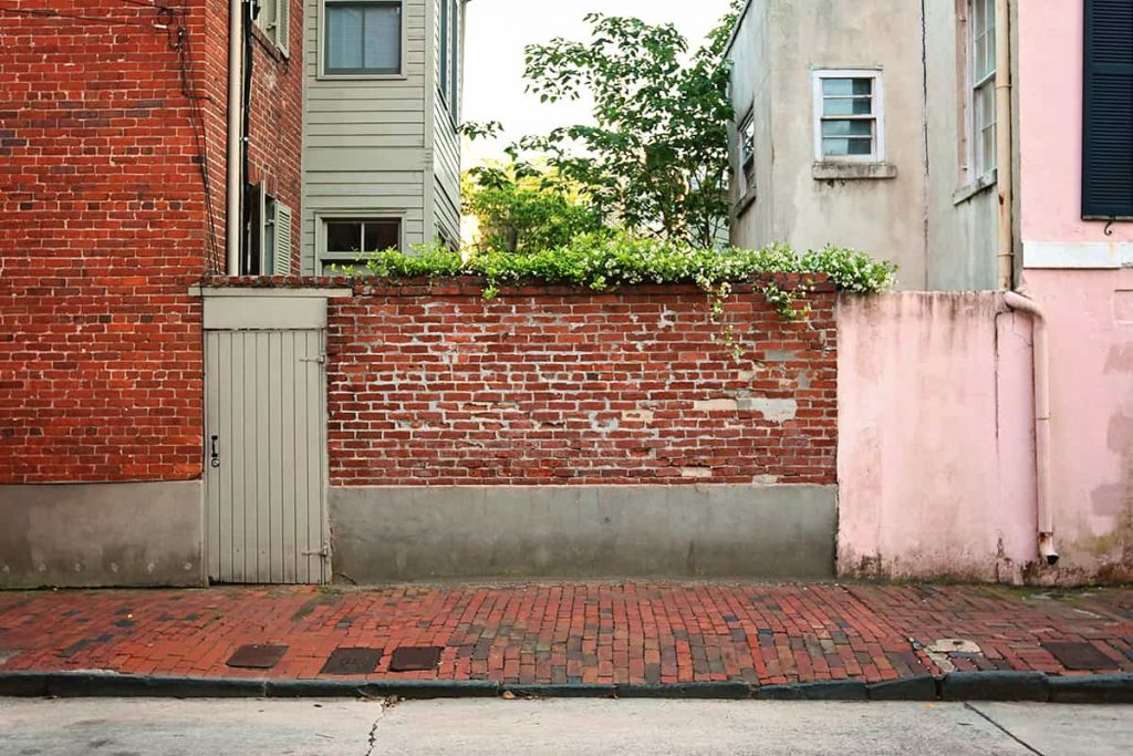 Pink house and red brick wall with Confederate Jasmine spilling over the top from a secret garden in Savannah's Historic District