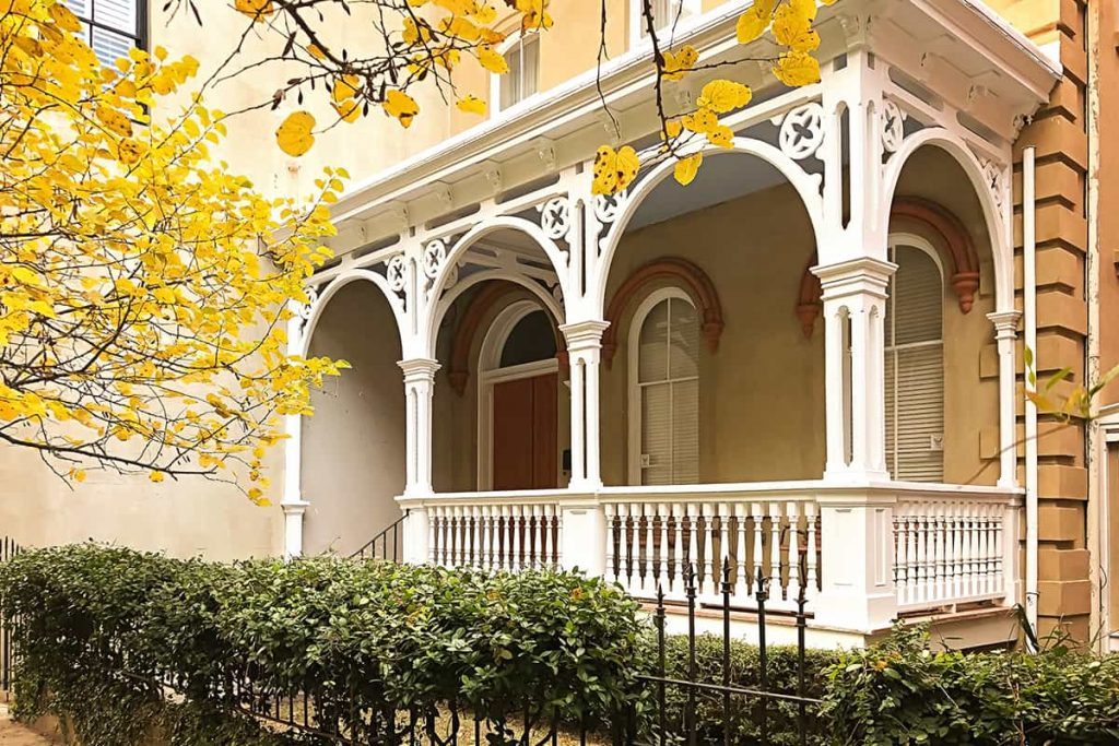 Yellow leaves surrounding an intricate Victorian porch on a home in Savannah