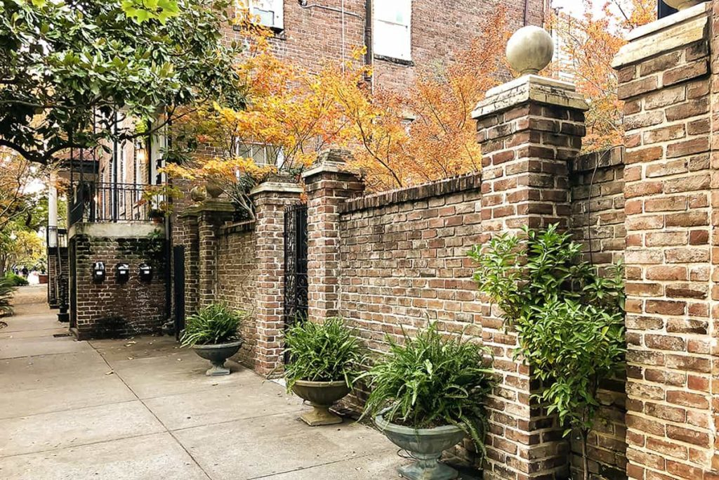 Fall foliage peeking over the wall of a hidden garden in Savannah's Historic District