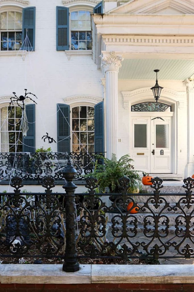 Multi-story mansion with pumpkins and fall decorations on the front porch